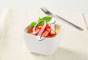 Small dish of vanilla pudding topped with strawberries