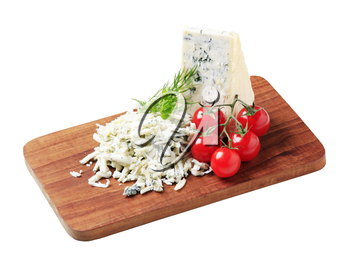 Blue cheese and fresh tomatoes on a cutting board
