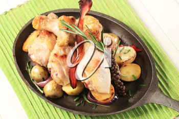 Chicken drumsticks and potatoes on a cast iron skillet