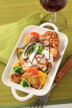 Baked potatoes and mixed vegetables topped with cheese
