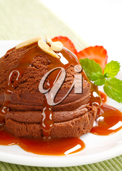 Scoop of chocolate ice cream with caramel syrup