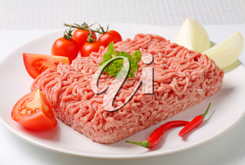 Raw ground pork and vegetables on plate