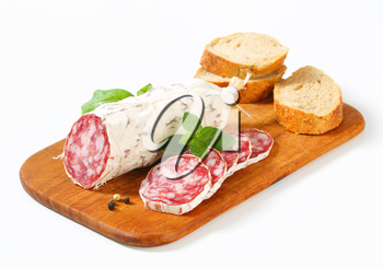 French Saucisson Sec and sliced crispy roll on cutting board