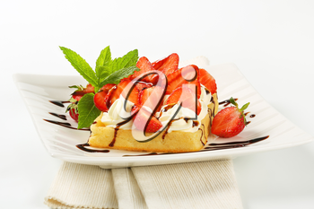 Belgian waffle with whipped cream and fresh strawberries