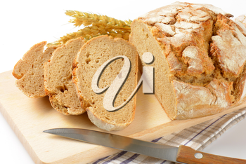 homemade bread and kitchen knife on wooden cutting board