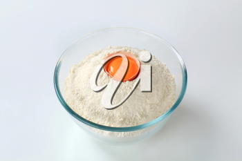 white wheat flour with cracked egg in a glass bowl