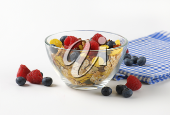bowl of mixed breakfast cereals with fresh raspberries and blueberries