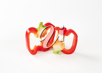 two slices of red bell pepper on white background