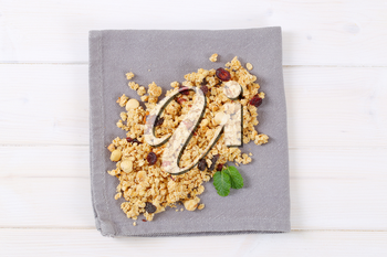 pile of morning granola with hazelnuts, raisins and cranberries on grey place mat