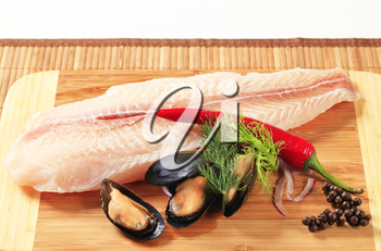 Fresh fish fillet and mussels on a cutting board
