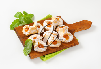 cookies with apricot jam filling on wooden cutting board