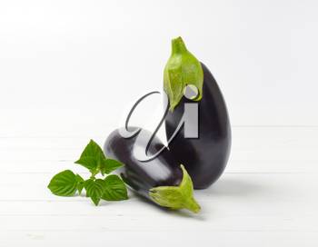 two fresh eggplants on white wooden background