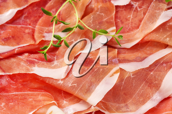 detail of air dried ham slices with thyme - full frame
