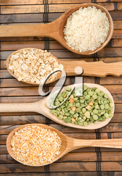 rice, pea and oat in spoon on table