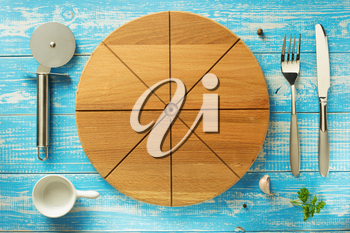 pizza cutting board and utensils at wooden table