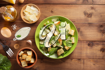 caesar salad and ingredients at wooden  background