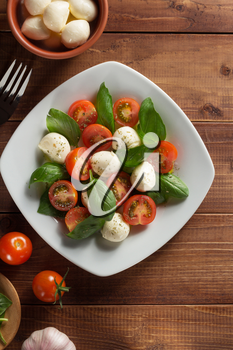 caprese salad in plate at wooden  background