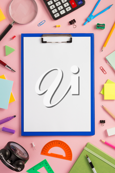 paper clipboard and school  supplies at abstract background surface