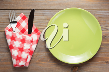 plate, knife and fork at rustic wooden plank board table background, top view