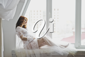 Beautiful girl in a white robe sitting on the windowsill.
