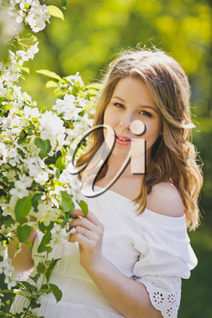 The girl in the position dressed in white resting in a beautiful garden.