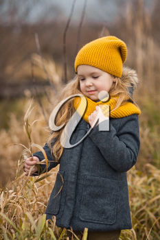 Little girl in a yellow hat and scarf walks along the shore of a river in autumn.