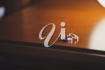 Wedding rings on the varnished table near the lamp.