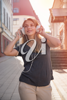girl with headphones listening to music on the street