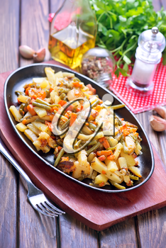 fried vegetables with meat on plate and on a table