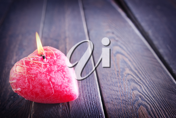 One red candle on the wooden table