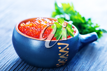 red salmon caviar with fresh parsley on a table