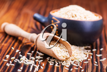 raw rice in wooden spoon and on a table