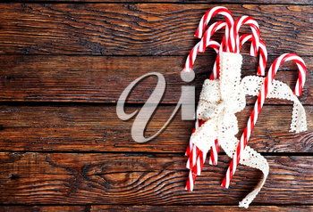 candycanes with white ribbon on the wooden table
