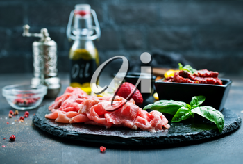Slices of Italian prosciutto crudo or jamon with fresh basil and dry tomato