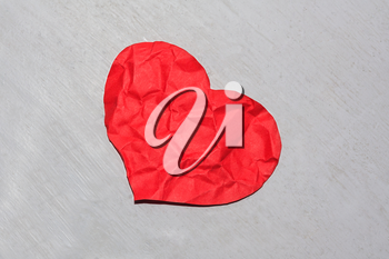 Abandoned crumpled red paper heart on a dirty shaded background