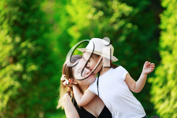 Daughter hugging her mother on the background of bright juicy green foliage. Happy family. Mom and child girl. Space for text. Shallow depth of field. Selective focus.