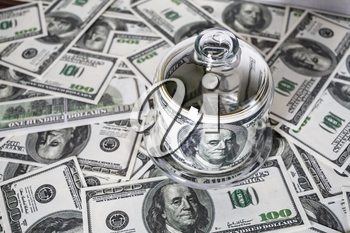 Money in a glass container on the background of one hundred dollar bills. Counterfeit money. Conceptual photo on the business theme. Selective focus.