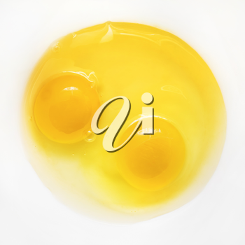Raw eggs on white plate. Two broken eggs. Yolk and white.