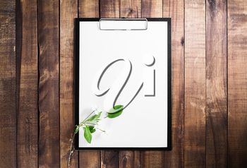 Paper clipboard on vintage wood table background. Blank letterhead and cherry blossoms with green leaves. Responsive design mockup. Top view.