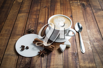 Coffee and spices. Coffee cup, cinnamon sticks, coffee beans, anise, sugar, spoon and coasters on vintage wood background.