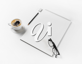 Blank stationery mockup. Notebook, glasses, coffee cup, pencil and eraser on white paper background. Template for placing your design.