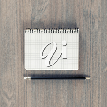 Blank notebook and pencil on wood background. Stationery mockup. Template for placing your design. Flat lay.