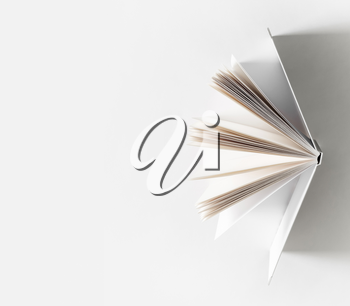Open book on white paper background. Space for text.