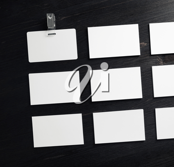 Blank white business cards and badge on wood table background. Flat lay.