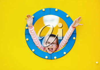 Happy girl in blue porthole on yellow background. Child has fun on the playground.