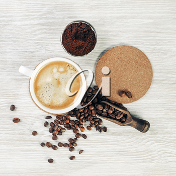 Photo of coffee cup, roasted coffee beans, ground powder and beer coaster on light wooden background. Flat lay.