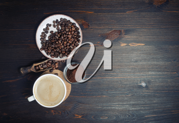 Vintage coffee background with space for text. Coffee cup, coffee beans and ground powder. Flat lay.