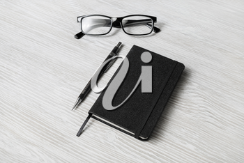 Photo of closed blank black notepad, glasses and mechanical pencil on light wood table background. Template for placing your design.