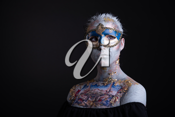 Portrait of a young masked woman with creative makeup on the theme of Venice Carnival