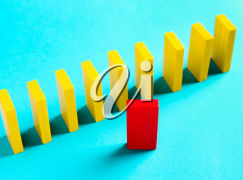 The concept of leadership, individuality. Red domino on yellow background